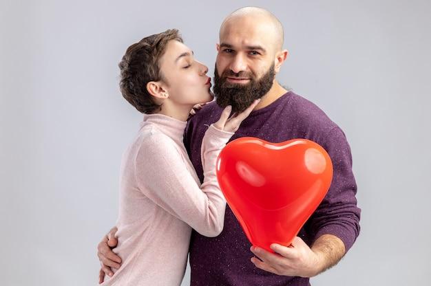 Jong koppel in casual kleding gelukkige vrouw kuste haar bebaarde vriendje met hartvormige ballon vieren valentijnsdag staande op witte achtergrond