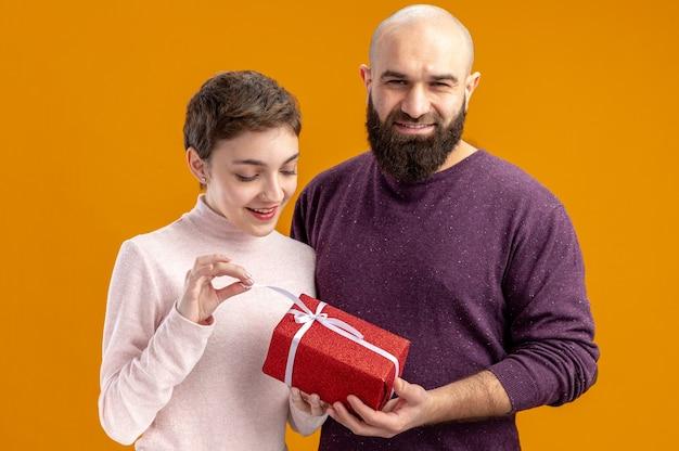 Jong koppel in casual kleding glimlachend bebaarde man een cadeau geven aan zijn verrast en gelukkig vriendin vieren valentijnsdag staande over oranje achtergrond