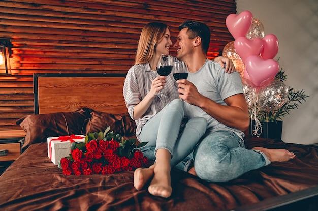 Jong koppel in de slaapkamer met glazen wijn, cadeau en rode rozen