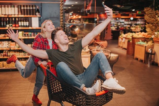 Jong koppel in de supermarkt. speelse man zit in trolley en zwaaien met handen.