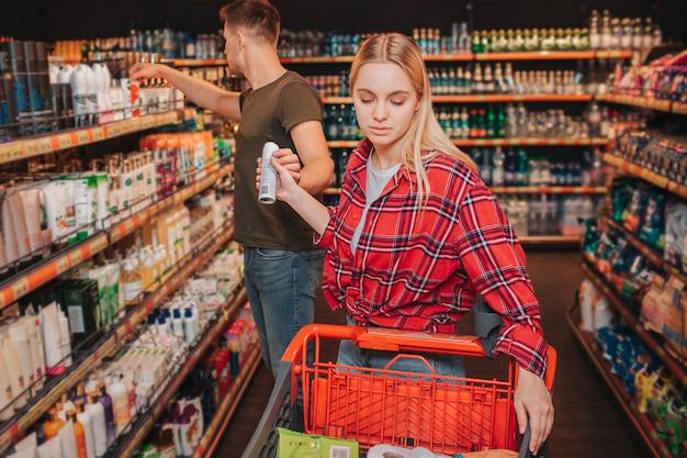 Jong koppel in de supermarkt. vrouw krijgt deodorant van man. hij kijkt naar de plank met hygiëneproducten. ze stopte het in de boodschappenwagen. ernstige geconcentreerde kopers.
