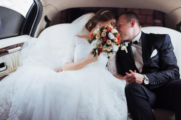 Jong koppel in een auto in trouwdag