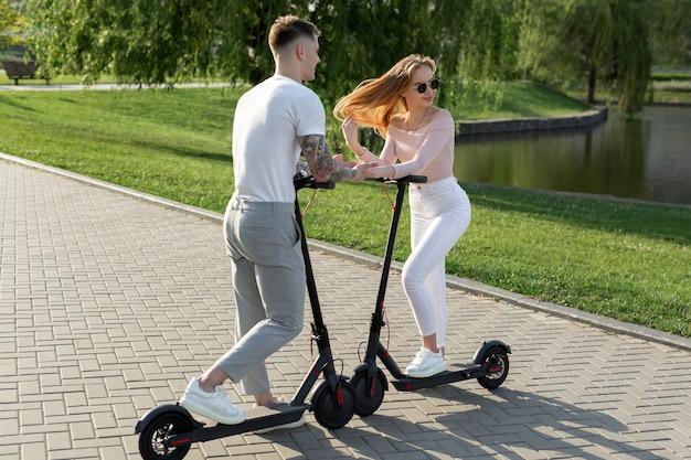 Jong koppel in het park op elektrische scooters