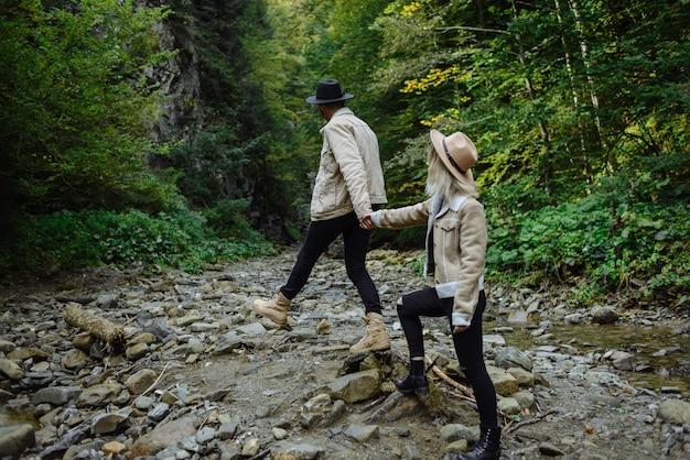 Jong koppel in jassen hand in hand en wandelen in een dennenbos. liefde in de natuur.