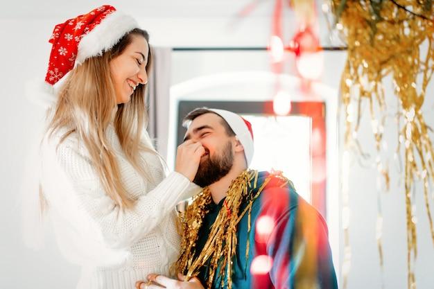 Jong koppel in kerstmuts siert het huis voor kerstmis en nieuwjaar