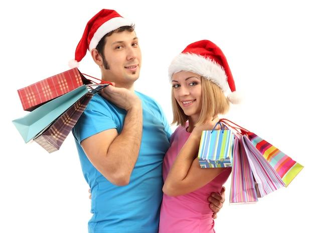 Jong koppel in kerstmuts winkelen en houden veel boodschappentassen geïsoleerd