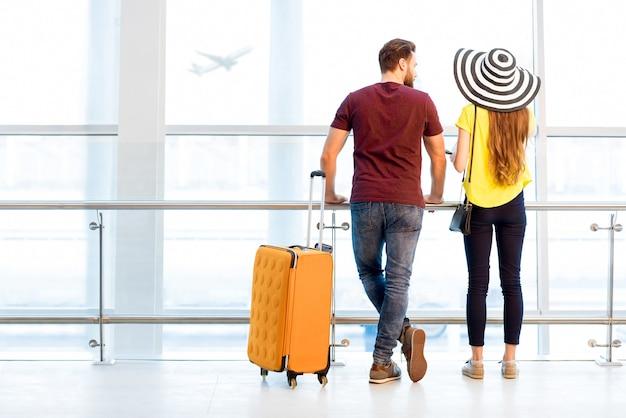 Jong koppel in kleurrijke t-shirts wachten met bagage bij het raam op het vertrekgebied van de luchthaven tijdens hun zomervakantie