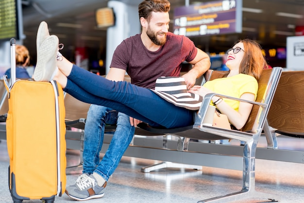 Jong koppel in kleurrijke t-shirts zitten met bagage in de wachtkamer van de luchthaven