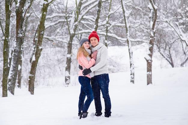Jong koppel in knuffels in sneeuw bos