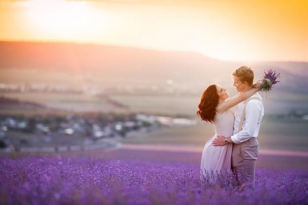 Jong koppel in liefde bruid en bruidegom, trouwdag in de zomer. geniet van een moment van geluk en liefde in een lavendelveld. bruid in een luxe trouwjurk.