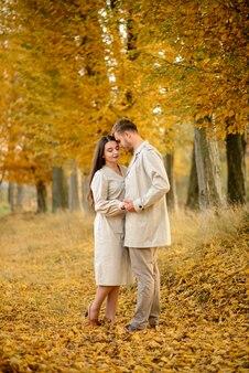 Jong koppel in liefde hand in hand en wandelen door een park op een zonnige herfstdag