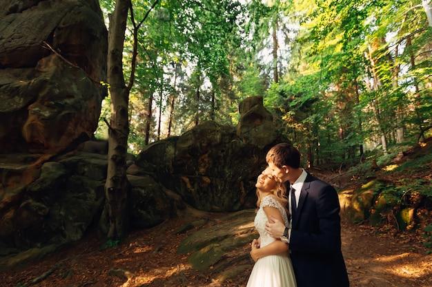 Jong koppel in liefde knuffelen in de herfst bos met rotsen