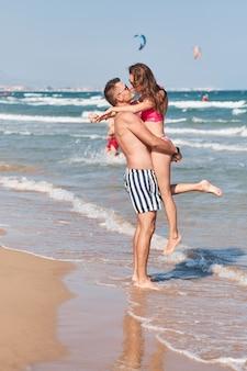Jong koppel in liefde met romantische tedere momenten op het strand.