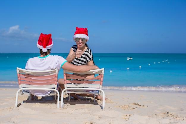 Jong koppel in santa hoeden tijdens strandvakantie