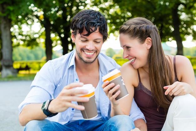 Jong koppel in stadspark koffie drinken