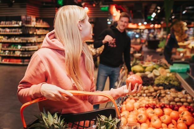 Jong koppel in supermarkt het nemen van fruit