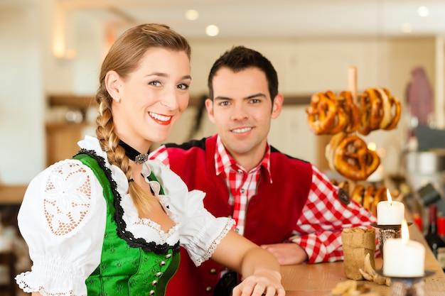Jong koppel in traditionele beierse klederdracht in restaurant of pub