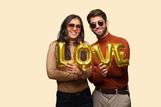 Jong koppel in valentijnsdag overschrijding van wapens, glimlachend en ontspannen