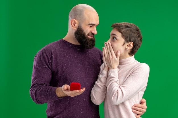 Jong koppel in vrijetijdskleding gelukkig en bebaarde man die voorstel met verlovingsring in rode doos aan zijn verbaasde vriendin tijdens valentijnsdag staande over groene achtergrond