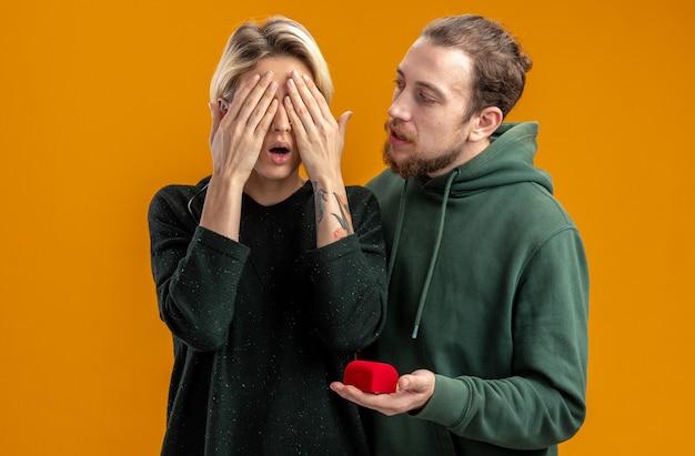 Jong koppel in vrijetijdskleding gelukkig man doet voorstel met verlovingsring in rode doos aan zijn vriendin die haar ogen bedekt met handen valentijnsdag concept staande over oranje achtergrond