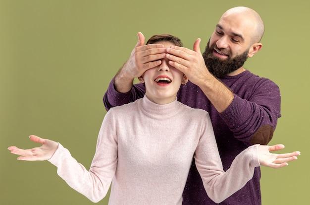 Jong koppel in vrijetijdskleding vieren gelukkig bebaarde man voor ogen van zijn lachende vriendin vieren valentijnsdag staande op groene achtergrond