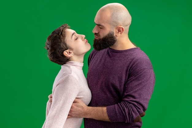 Jong koppel in vrijetijdskleding vrouw met kort haar en bebaarde man gelukkig verliefd samen omarmen gaan kussen vieren valentijnsdag staande op groene achtergrond