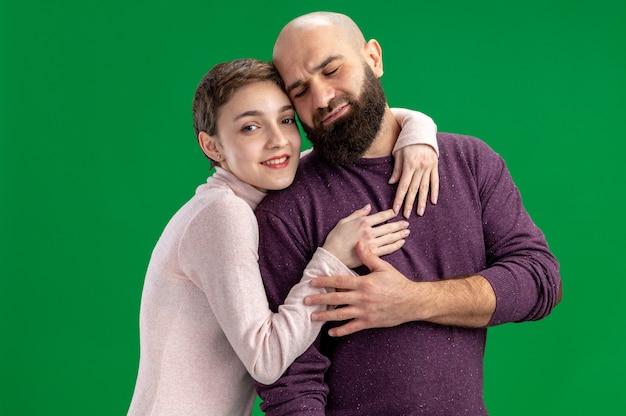 Jong koppel in vrijetijdskleding vrouw met kort haar en bebaarde man gelukkig verliefd samen omarmen vieren valentijnsdag staande op groene achtergrond