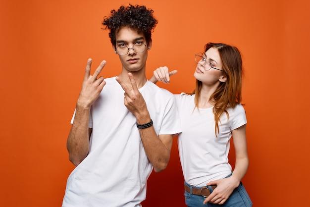 Jong koppel in witte t-shirts en glazen leuke mode-sinaasappel