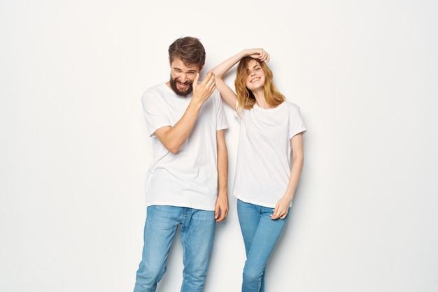 Jong koppel in witte t-shirts en jeans vriendschap op emoties mockup