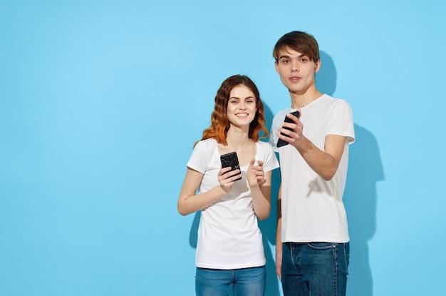 Jong koppel in witte t-shirts met telefoons in handen communicatietechnologie