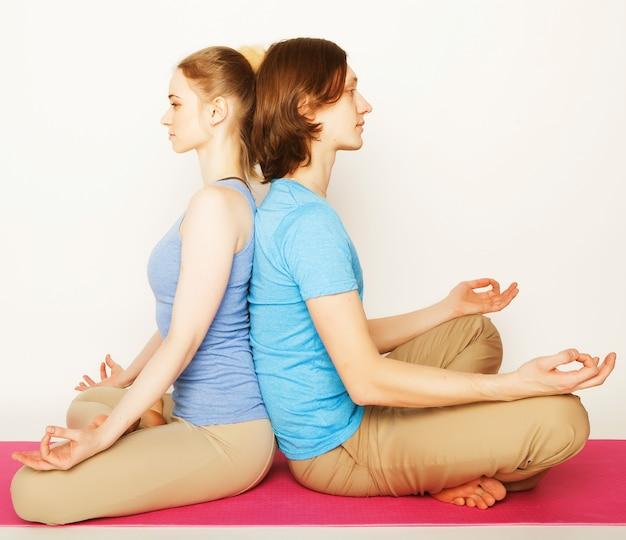 Jong koppel in yoga pose, gelukkige familie