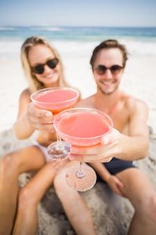 Jong koppel in zonnebril met cocktailglas op het strand