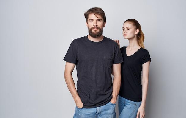 Jong koppel in zwarte t-shirts en spijkerbroek studio elegante levensstijl