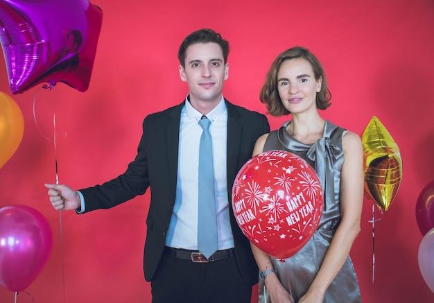 Jong koppel is blij met kleurrijke ballonnen naast hen en de rode muur in het concept van nieuwjaar en eerste kerstdag.