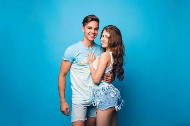 Jong koppel is knuffelen op blauwe achtergrond in de studio. ze dragen t-shirts, spijkerbroeken en glimlachen naar de camera.