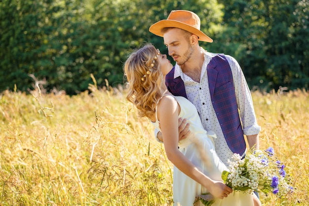 Jong koppel jongen en meisje in het veld knuffelen, romantische relatie concept