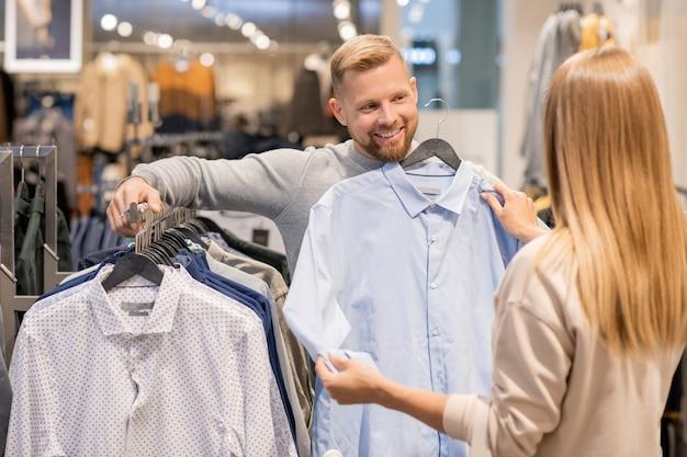 Jong koppel kiezen nieuw shirt voor man terwijl je door rek met nieuwe collectie in kledingafdeling in het winkelcentrum