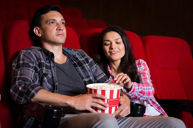 Jong koppel kijken naar film in de bioscoop
