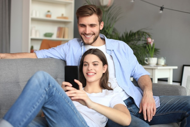 Jong koppel kijken naar online inhoud in een smartphone zittend op een bank thuis in de woonkamer