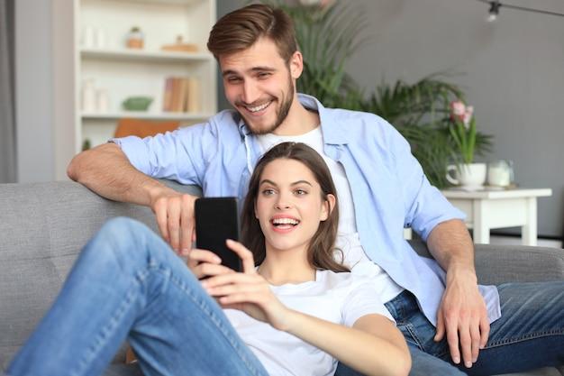 Jong koppel kijken naar online inhoud in een smartphone zittend op een bank thuis in de woonkamer.
