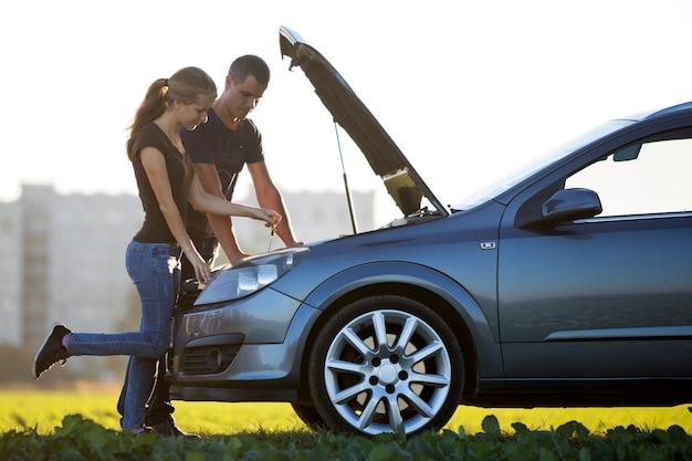 Jong koppel, knappe man en aantrekkelijke vrouw op auto met popped kap oliepeil in motor controleren. transport, voertuigen problemen en storingen concept.