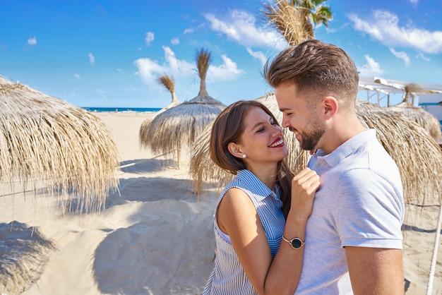Jong koppel knuffel in een strand met parasol
