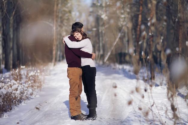 Jong koppel knuffelen elkaar in de winter in het park. liefdesverhaal