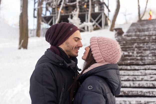 Jong koppel knuffelen elkaar in winter park met sneeuw