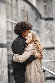 Jong koppel knuffelen in de straat jassen dragen.