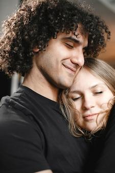 Jong koppel knuffelen met gesloten ogen.