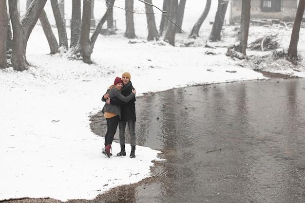 Jong koppel knuffelen naast een rivier