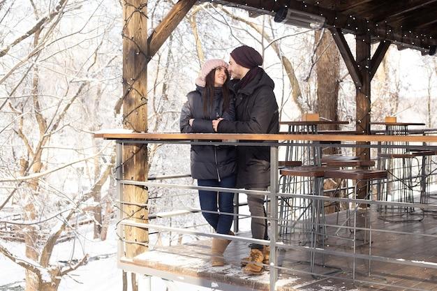 Jong koppel knuffelen op besneeuwde park in winterweer