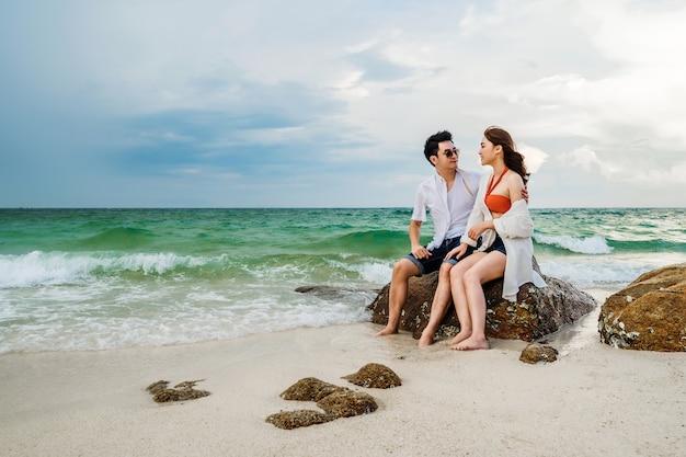 Jong koppel knuffelen op de rots van zee strand op koh munnork island, rayong, thailand