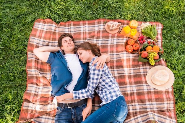 Jong koppel knuffelen op deken tijdens picknick
